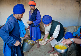 A nihang warrior serves food to the fellow nihangs.