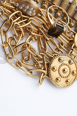 Pile of gold jewelry - ring, necklaces, bracelet, earclips with copy space on white background..Studio Shot