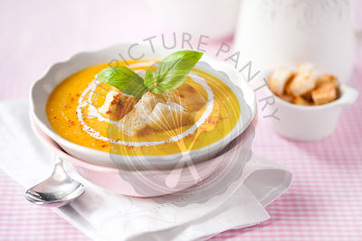 Pumpkin soup with croutons, cream and basil