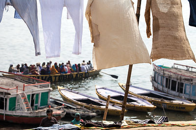 A boat full of pilgrims on the Ganges River passes by laundry drying near Prayag Ghat, Varanasi, India.