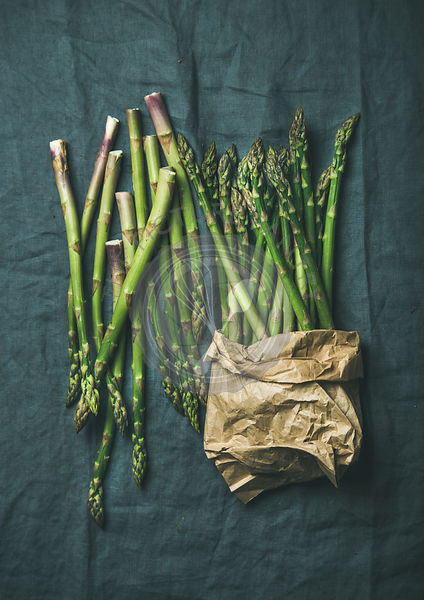 Fresh green asparagus in craft paper bag over dark grey linen table cloth background