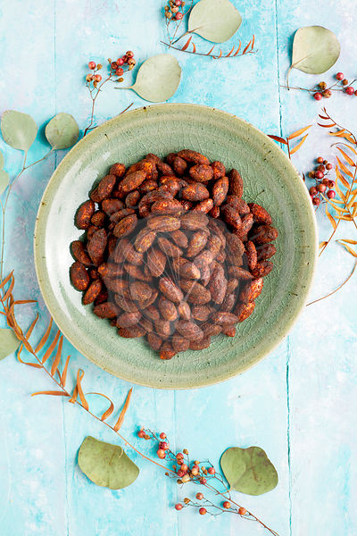 Pink Peppercorn Cacao Almonds. Photographed on a light blue background.
