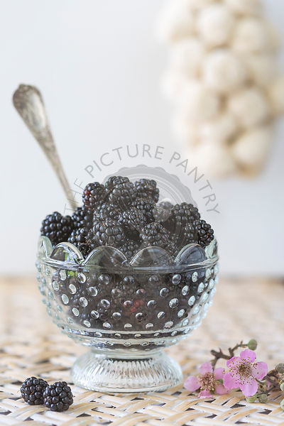 blackberries in glass dish on woven tray with vintage spoon