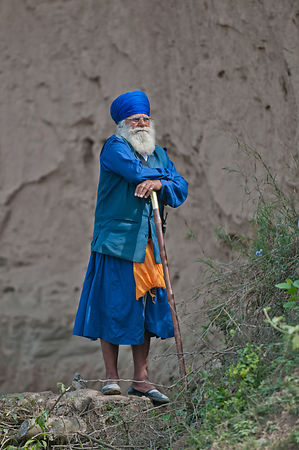 An old nihang warrior stands on a raised platform to get a glimpse of the games during the festival of holla mohalla.