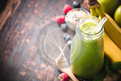 Close-up of green fresh smoothie with fruits, berries, oats and seeds, selective focus. Detox, dieting, clean eating, vegetarian, vegan, fitness, healthy lifestyle concept