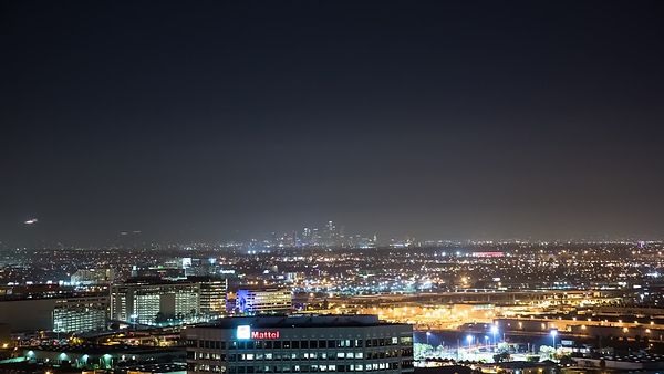 Bird's Eye: Landing Airplanes In Front of Distantly Lit DTLA Skyline