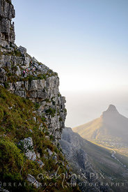 Hikers on a ledge on Table Mountain, city and Lion's Head, Robben Island below.