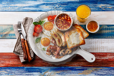 English breakfast in white pan with fried eggs, sausages, bacon, beans, toasts and orange fresh on wooden background