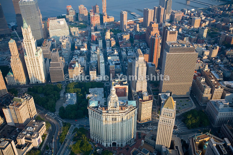 An aerial view of Civic Center in Lower Manhattan.  The Municipal Building is in the center.  The U.S. Courthouse, with a pyramidal roof, is to the right, and to the left is City Hall.  The Woolworth Building is on the upper left, and the modern rectangular building is the Javits Federal Office Building, on the right.
