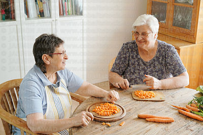 Senior friends cooking together at home, cutting carrots on an old wood table