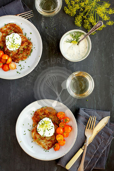 Potato Provolone Cakes served with Dill Creme, Cherry Tomatoes, Kale and White Wine. Photographed on a grey background.