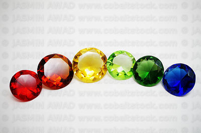 Glass diamonds in rainbow colours on a grey background with copy space