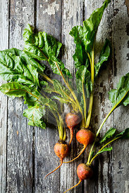 Beets with leaves on a vintage wooden table background