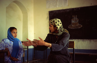 A teacher adresses schoolgirls in a classroom in Mazar-i-Sharif, Afghanistan