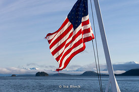 Mountain scene in Frederick Sound in Southeast Alaska with the American flag blowing in the wind.