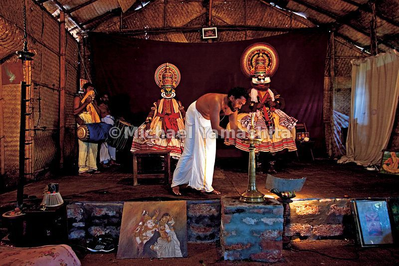 Kathakali actors in Kerala prepare for a performance as a troupe member lights an oil lantern.