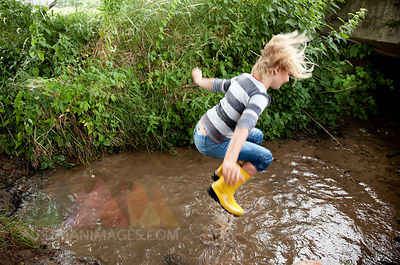 Excited girl jumping into brook