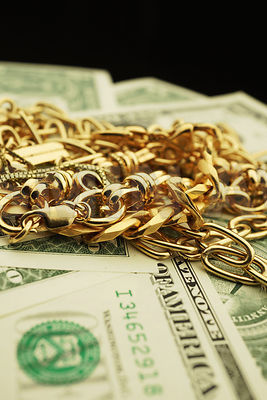 Gold jewelry and money with lots of copy space