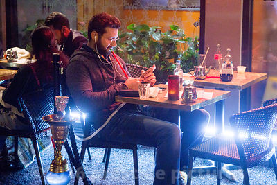 Man at restaurant table Smoking a Nargile whilst watching a film on his smart phone