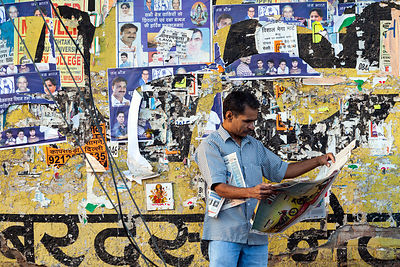 India - New Delhi - A man reads a newspaper by a wall with political posters