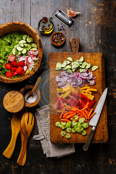 Sliced fresh vegetables on cutting board and salad in olive wood bowl on wooden background