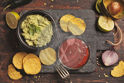 Mexican nachos chips with homemade fresh guacomole sauce and salsa over old background. Top view. Mexican food concept