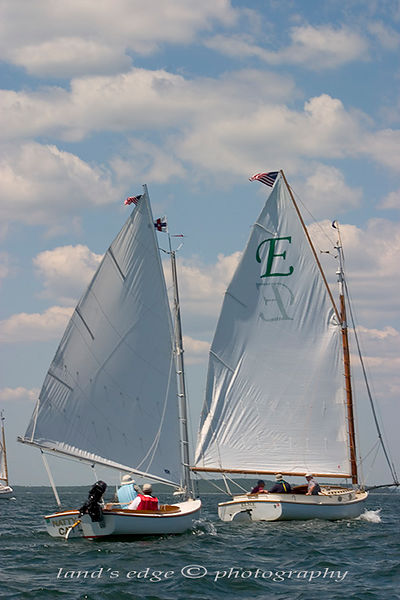 Natty Cat, a Marshall Sandpiper, trails Elsie, a Marshall 22 closely on the long reach to Mashnee Island off Bourne.  the two catboats were among 18 participating in the annual Catboat Association rendezvous out of  Squeteague Harbor.