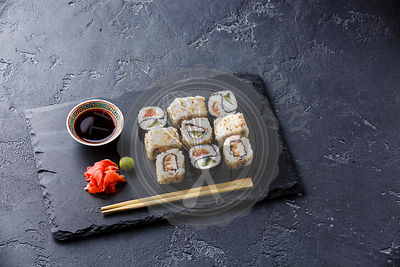 Sushi rolls Yin Yang shape on stone slate on black stone background copy space