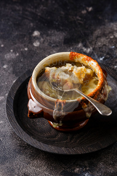Authentic French Onion soup with dried bread and cheddar cheese in bowl on dark background copy space