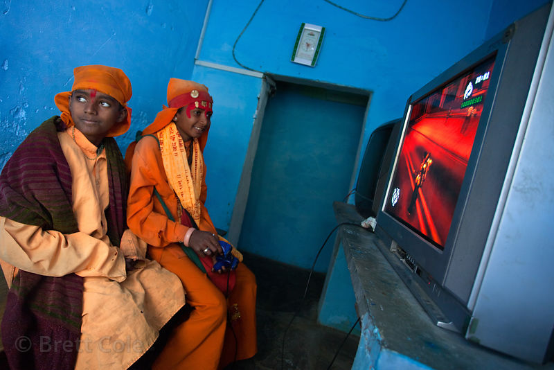 Two boys pretending to be sadhus (holy men) to get money from tourists, playing Grand Theft Auto video game, Pushkar, Rajasthan, India