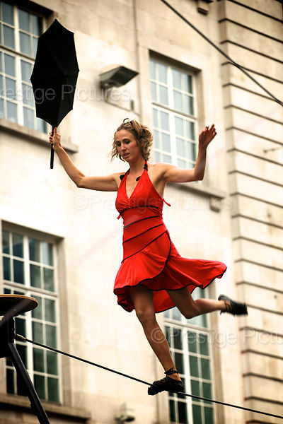 Woman in Red Dress Walks a Tightrope Holding an Umbrella