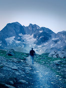 Hiker at dawn in mountain landscape