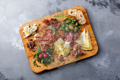 Italian snacks food with Ham, Olive, Cheese, Sun-dried tomatoes, Sausage and Bread on wooden cutting board on concrete background