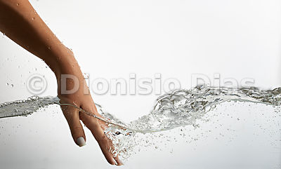 Hand creating ripples on water surface