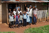 Happy family outside house in Kenya, waving and smiling.
