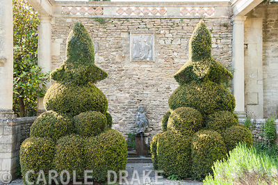 Clipped yews frame the Blue Pool, a small formal pool, with a Romanesque bas relief set into the wall above of a woman riding a lion. Iford Manor, Bradford-on-Avon, Wiltshire