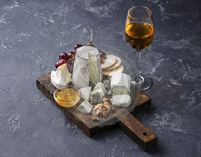 Goat Cheese board Snack assortment with confiture and grape on cutting board and wine on black background