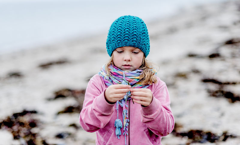 Little Danish girl in a blue hat at the beach in autumn 9