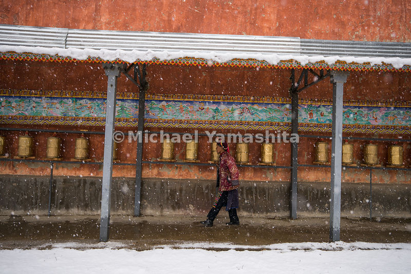 A villager walks past bronze prayer wheels lining a wall of the Fei Lai Shi temple, a Buddhist shrine in Yunnan's snowy backcountry. Spinning a prayer wheel is thought to increase the power of prayer.