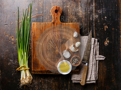 Wooden cutting board background with seasoning, herbs and kitchen knife on wooden background copy space