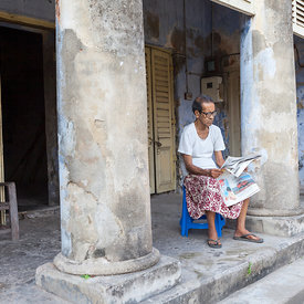 Dilip Kumar Chaterjee, 77 reads the newspaper on the porch of his house that has been in his family for three generations