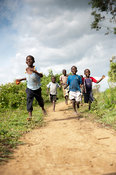 Happy children running barefoot down a dirt path, Kenya.