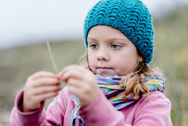 Little Danish girl in a blue hat at the beach in autumn 8
