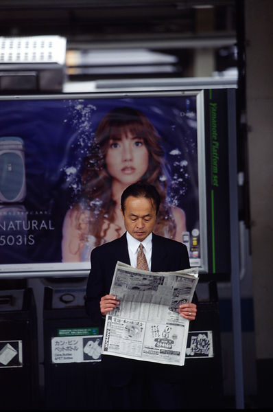A business man reads a newspaper in front of a fashion advertisement with a woman's face. Tokyo, Japan