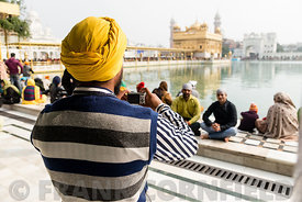 Sikh taking photograph of friends sitting at the lake ofthe Golden Temple in Amritsar.