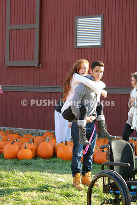 Young paraplegic woman selecting pumpkins with her boyfriend for Halloween