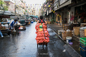 A worker carrying onions at Pak Khlong Market (Flower Market) in Bangkok, Thailand.