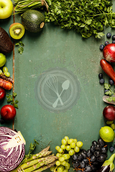Assortment of raw organic fruits and vegetables: eggplants, onions, berries, carrots, grapes, cabbage, avocado, plums over rustic background, gluten free, allergy-friendly, clean eating or raw diet. Top view with space. Food frame