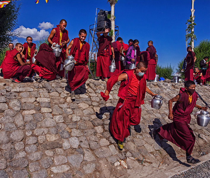 A group of monks run to get tea during a festival in a Ladakhi monastery.