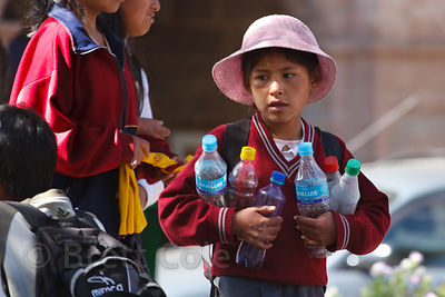 A girls collects plastic bottles to be recycled for money in Cusco, Peru
